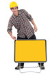 Construction worker pointing to a blank yellow sign
