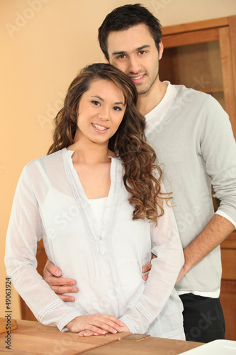 Young couple standing in their new home