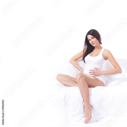 A young pregnant woman in white lingerie on a sofa