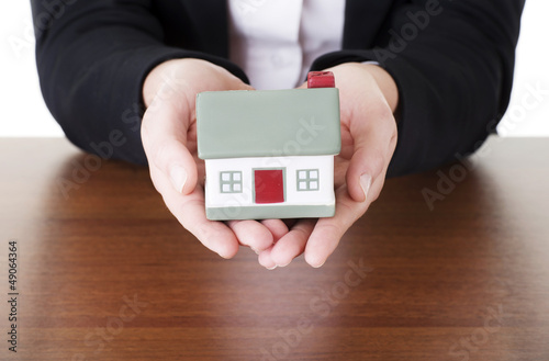 Female businesswoman hands holding house.