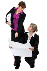 two real estate businesswomen looking at a blueprint