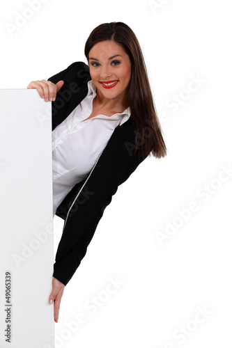 Brunette woman peeking behind a white panel