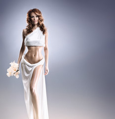 A young redhead Caucasian woman posing in a white dress