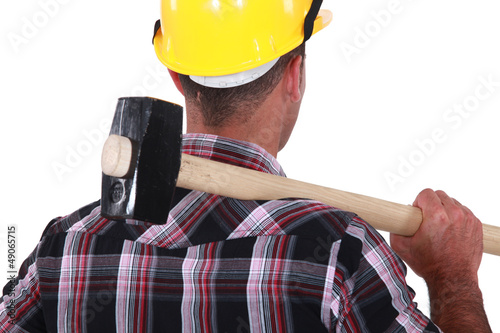 Worker resting large hammer over shoulder