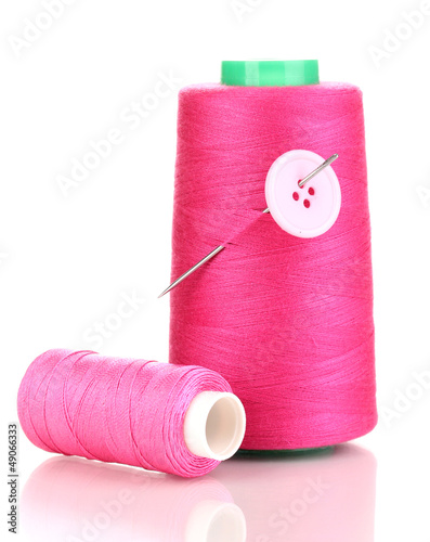 Pink bobbin with needle and buttons isolated on white