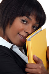 Businesswoman holding folder against face