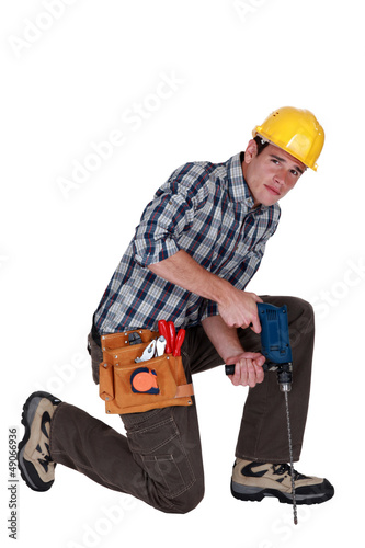 Man drilling into the floor