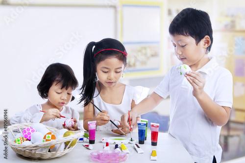 Children painting easter eggs in art class