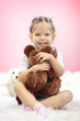 Cute little girl playing with toy bear, on pink background