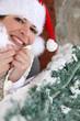 Festive woman stood in Santa hat by tree