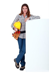 A female construction worker by a billboard.