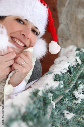 Festive woman stood in Santa hat by tree