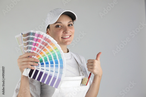 Smiling woman painter holding swatches