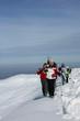 Group of skiers walking across a mountain ridge