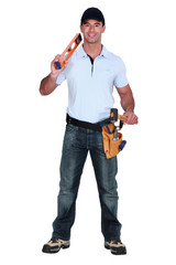 Builder holding spirit level and hammer