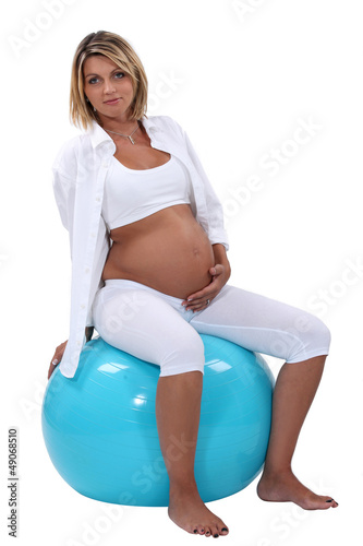 Pregnant woman holding her tummy and sitting on an ball