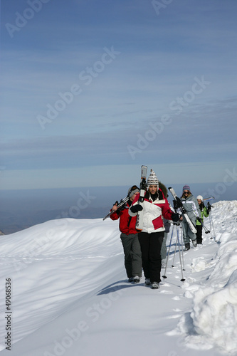 Group of skiers walking across a mountain ridge