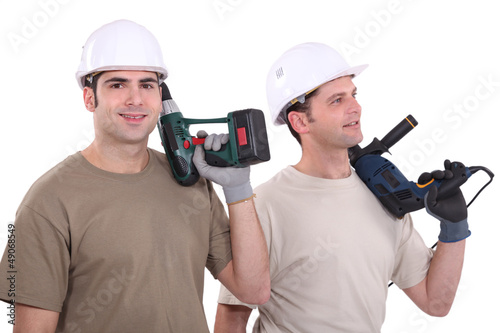 Two male builder with drills