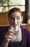 Young Woman with Beautiful Auburn Hair Drinking Water poster