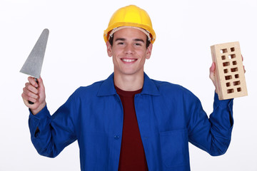 craftsman holding a brick and a trowel