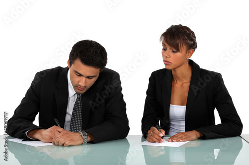 Two businesspeople writing at a desk