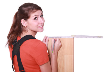 female woodworker measuring a board