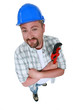 Cheerful plumber holding adjustable wrench