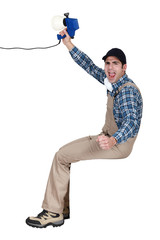 A handyman holding a speaker.