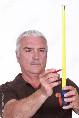 Man using tape measure and pencil