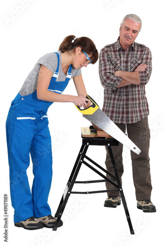Female apprentice sawing wood