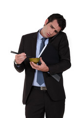 Businessman trying to eat noodles while talking on the phone