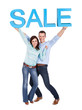 Happy young couple holding sale sign