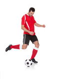Professional soccer player kicking ball