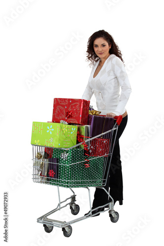 Woman with a shopping trolley full of presents