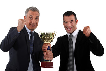 businessmen holding a golden cup