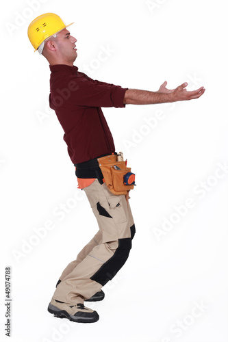 Construction worker carrying something heavy