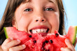 Happy young girl eating watermelon