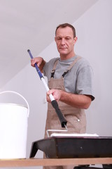 Decorator dipping his ceiling roller into a tray of white paint