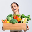 Joyful woman with box crate of fresh vegetables produce