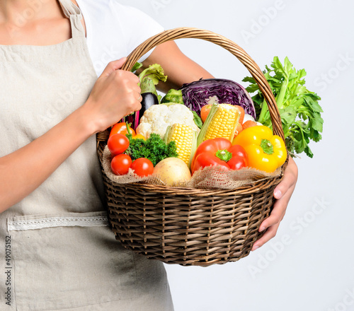 Smiling woman with fresh produce basket full of vegetables