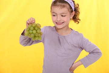 Little girl holding grapes