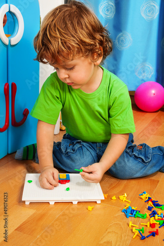 Little boy solving puzzle