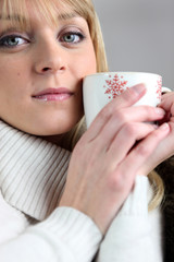 young woman having warm beverage