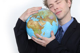 Businessman hugging globe