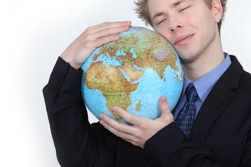 Businessman hugging globe