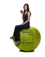 Asian Woman Sitting on Red Delicious Apple with Nutrition Label
