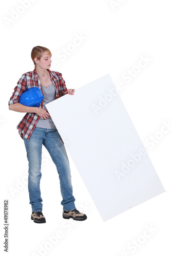 Female builder holding poster