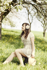 Beautiful girl sitting on suitcase at outdoors
