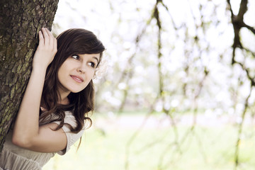 Beautiful young woman hiding behind tree trunk