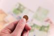 1 Cent in der Hand mit Banknoten im Hintergrund